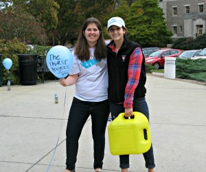 Two students holding containers of water as part of the Thirst Project.